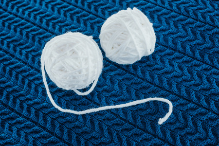 흰색 원사 공과 뜨개질 바늘
