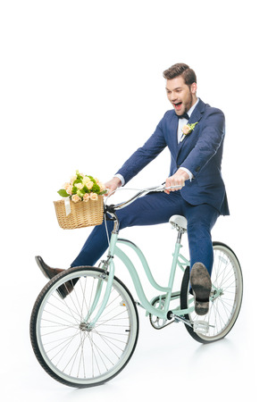 happy groom in suit riding retro bicycle with wedding bouquet in basket