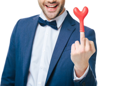 cropped shot of cheerful man wearing heart shaped balloon on middle finger Foto de archivo