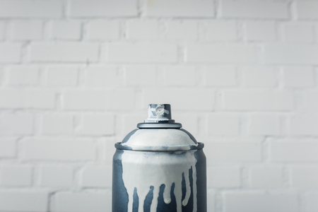 aerosol paint in can with white brick wall background