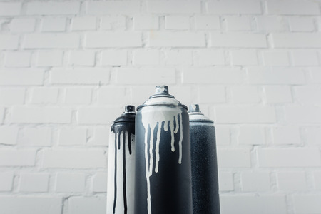 spray paint in cans with brick wall background