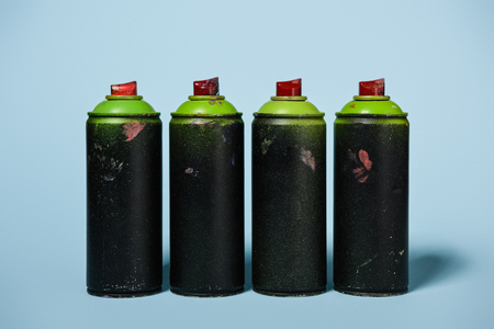 arranged cans with aerosol paint isolated on blue