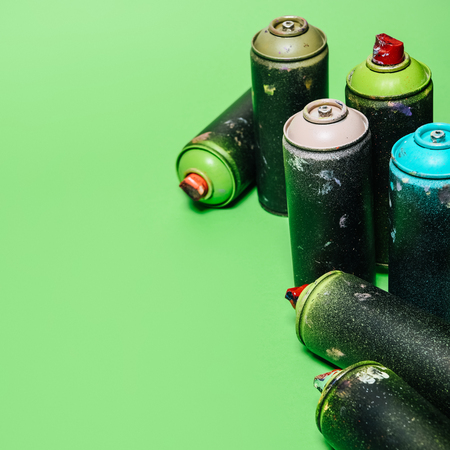 arranged cans with aerosol paint isolated on green Stok Fotoğraf