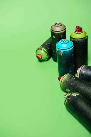 arranged cans with aerosol paint isolated on green Reklamní fotografie