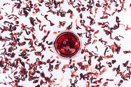 top view of cup with hibiscus tea between scattered tea
