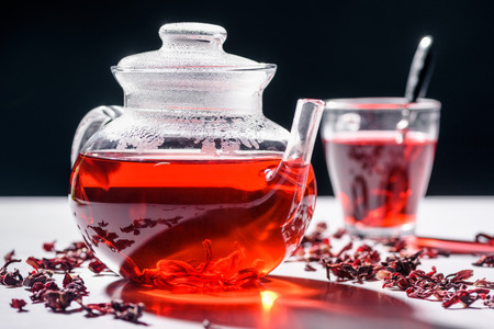 glass teapot with hibiscus tea and cup with spoon