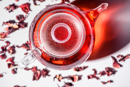 top view of transparent glass teapot with hibiscus tea and scattered tea Stock Photo