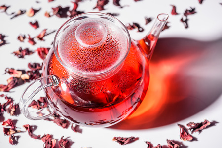 transparent glass teapot with hibiscus tea and scattered tea