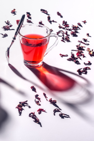 glass cup of hibiscus tea with spoon and scattered tea Stock Photo