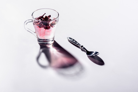 glass cup of hibiscus tea with spoon