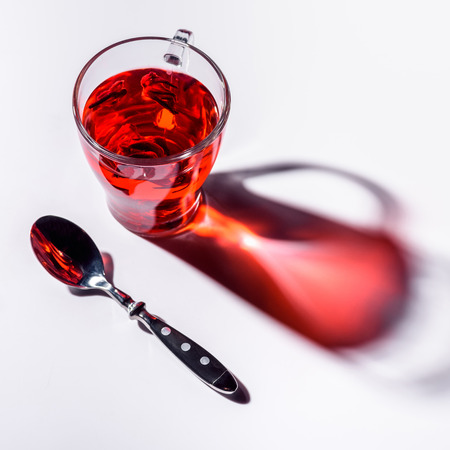 high angle view of glass cup with hibiscus tea and spoon