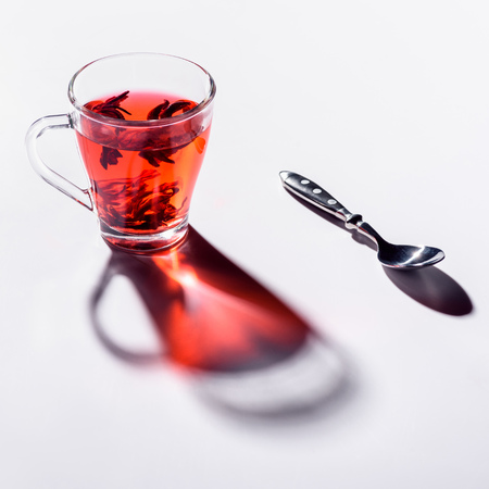 glass cup with hibiscus tea and spoon