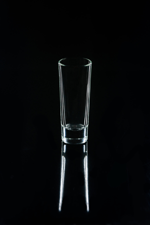 small glass on black reflecting surface