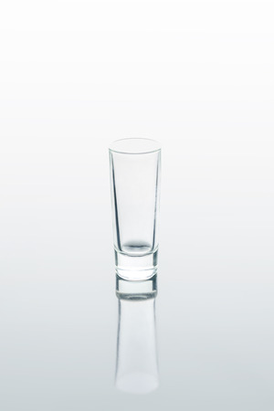 small glass on white reflecting surface