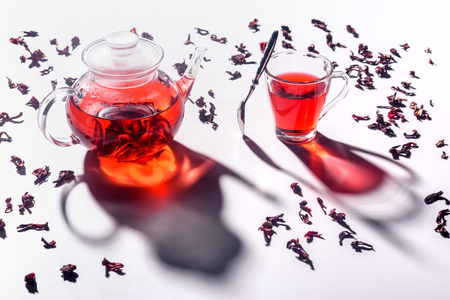 high angle view of glass teapot with hibiscus tea and cup with spoon