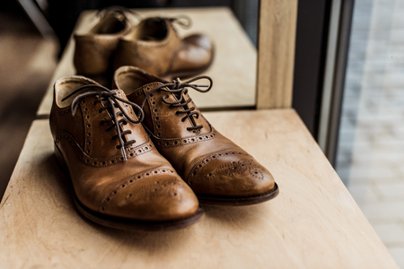 brown male shoes at showcase in shop