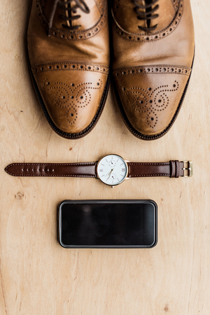 shoes, smartphone and watch on wooden surface
