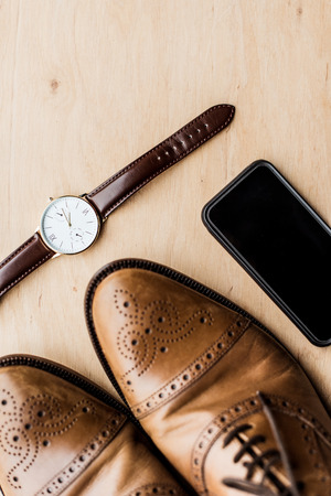 watch, smartphone and shoes on wooden table