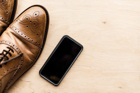 smartphone and brown leather shoes on wooden surface