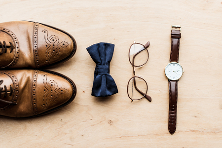 Shoes, tie bow with glasses and watch on wooden floor