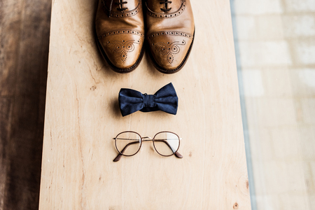 Shoes, tie bow and glasses on wooden stand