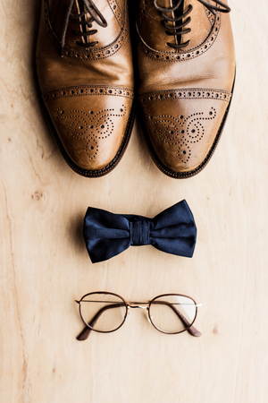 shoes, tie bow and glasses on wooden floor
