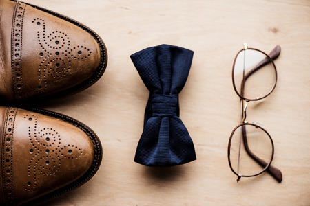 shoes, tie bow and glasses on wooden surface