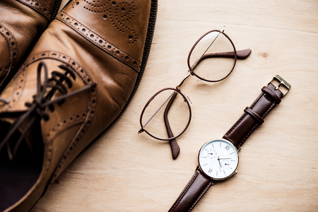 brown shoes, glasses and watch on wooden surface