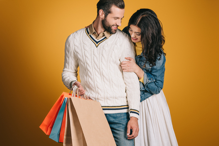 couple with shopping bags isolated on yellow