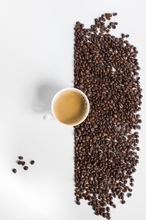 top view of cup of coffee and scattered coffee beans
