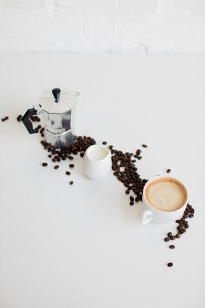 Franse pers, kopje koffie en melk pot met verspreide koffiebonen