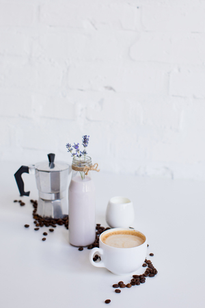 french press, cup of coffee, milk jar and lavender drink with scattered coffee beans