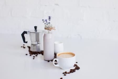 Franse pers, kopje koffie, melkkan en lavendeldrank met verspreide koffiebonen
