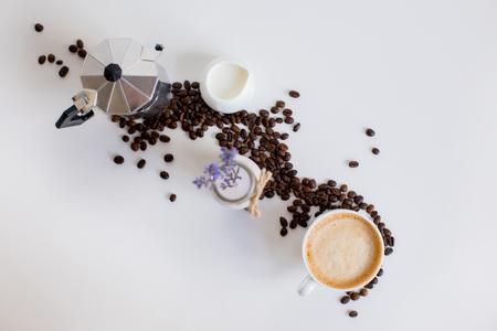 bovenaanzicht van Franse pers, kopje koffie, melk pot en lavendel drankje met verspreide koffiebonen