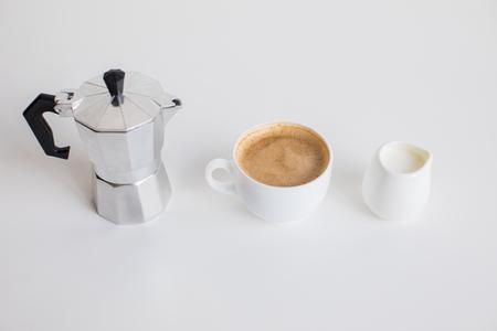 Franse pers, kopje koffie en melk pot staan in de rij Stockfoto