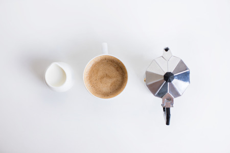 top view of french press, cup of coffee and milk jar standing in row