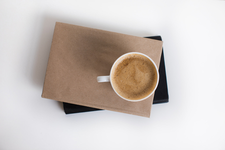 bovenaanzicht van witte kop koffie op twee boeken
