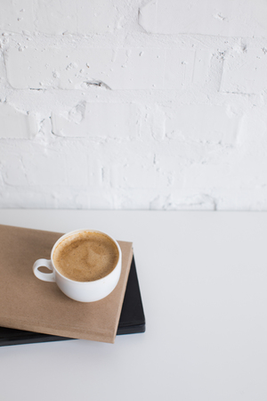 white cup of coffee on two books on white tabletop with copy space