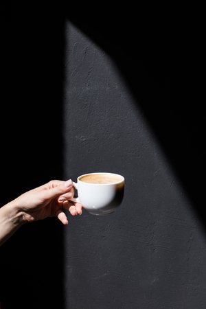 cropped view of person holding cup of coffee