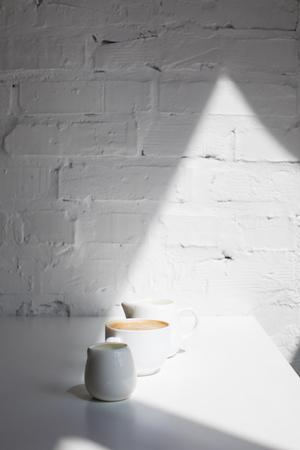 kopje koffie en melk potten in rij Stockfoto