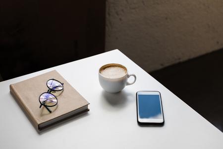 kopje koffie, brillen, smartphone en Kladblok Stockfoto