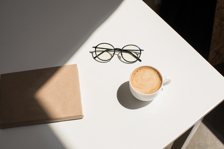 cup of coffee, eyeglasses and notepad on white table with sunlight