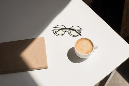 kopje koffie, brillen en Kladblok op witte tafel met zonlicht