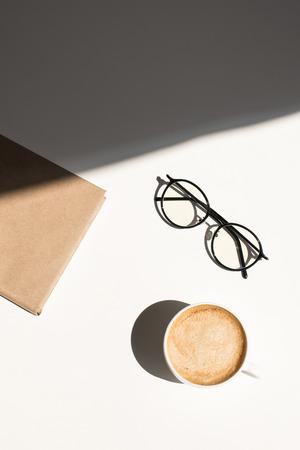 kopje koffie, brillen en Kladblok op wit tafelblad met zonlicht