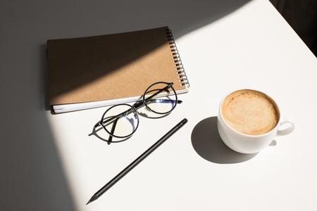 kopje koffie, brillen en Kladblok