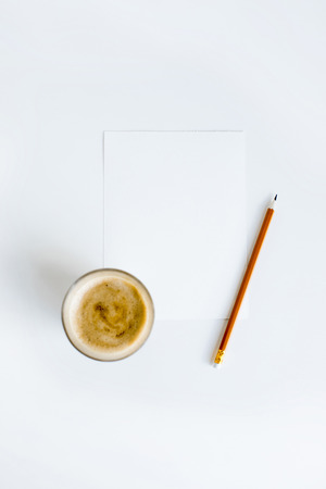 top view of cup of coffee on white paper with pencil Stockfoto