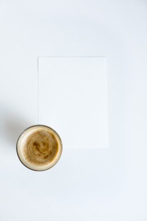 top view of cup of coffee on white paper with copy space,