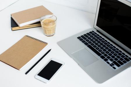 laptop, smartphone, notitieblok, boeken en een glas koffie