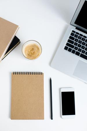 bovenaanzicht van laptop, smartphone, kladblok, boeken en glas koffie