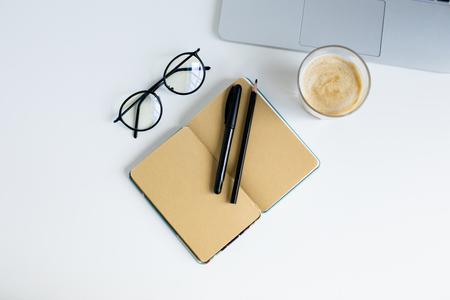 bovenaanzicht van laptop, notitieblok, brillen en glas koffie,